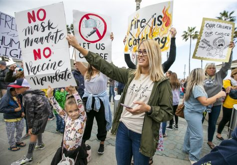 Parents rally with posters and chants in Huntington Beach to protest the public school vaccine mandate.