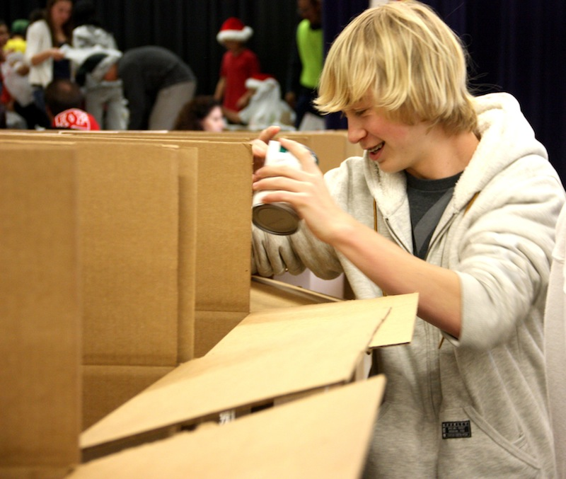 Freshman Cameron Karbum one of many who helped on Friday to sort cans collected during the Cheers for Children drive. Credit: Megan Kearney/The Foothill Dragon Press.
