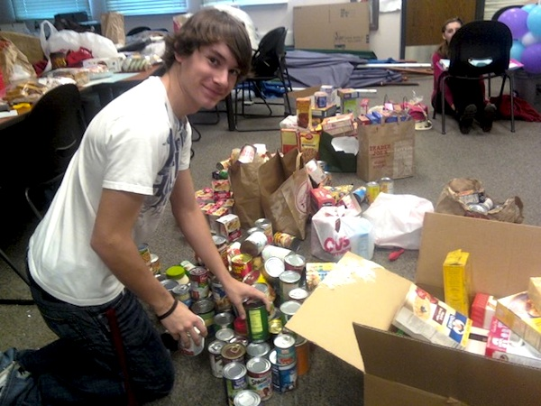 Junior Trevor Kirby organizes canned food donated by students for the Cheers for Children food drive. Credit: Caitlin Trude/The Foothill Dragon Press.