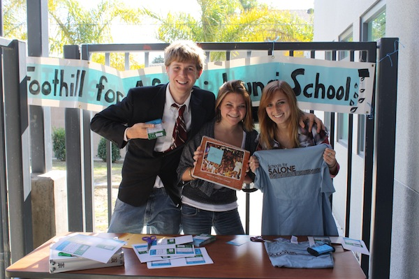 Seniors Loren Hansen, Lindsey Manset and Caroline Frambach sell concert tickets and Schools for Salone t-shirts outside Mrs. Eulaus classroom to raise money for a school that will be built in Lungi. Photo Illustration: Emma Huebner/The Foothill Dragon Press.