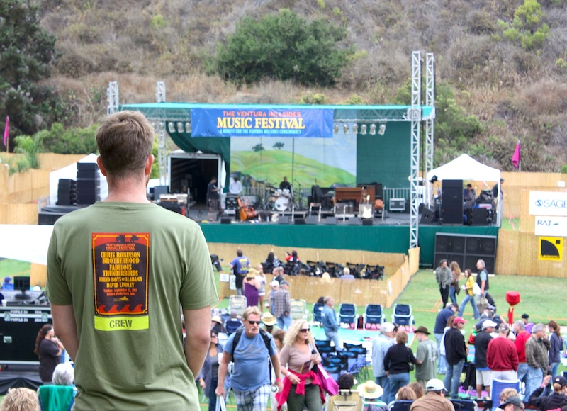 A crew member overlooks people gathering at the Hillsides Music Festival on Sunday. Credit: Megan Kearney/The Foothill Dragon Press.