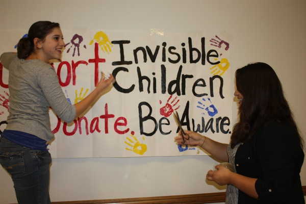 Seniors Karen Fox and Molly Roberts volunteer with the rest of the Invisble Children club to raise awareness about child soldiers at Spirito Hall on Thursday, December 9th. Photo Credit: Lauren Parrino/ The Foothill Dragon Press.