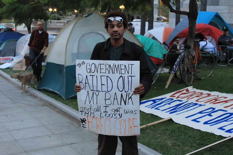A man protests the distribution of wealth at a similar protest in Los Angeles. Credit: Ben Gill for The Foothill Dragon Press