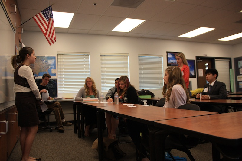 Freshman Patricia McCoy (left) answers a question from Daisy Myring (far right) about why food companies hide the ingredients in their products at Monday's Ninth Grade Project presentation. Credit: Felicia Perez/The Foothill Dragon Press