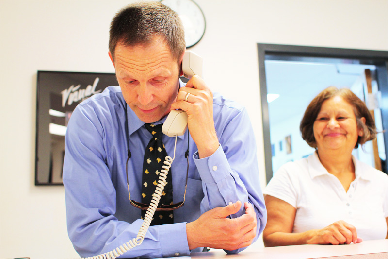 Principal Joe Bova announces that Foothill was named a Blue Ribbon School over the intercom on Monday morning while office manager Liz Prado watches over his shoulder. Credit: Aysen Tan/The Foothill Dragon Press