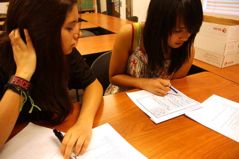 Freshman Emma Saldana takes a peek at freshman Joanne Quirays test answers. Photo illustration: Otto Tielemans/The Foothill Dragon Press.