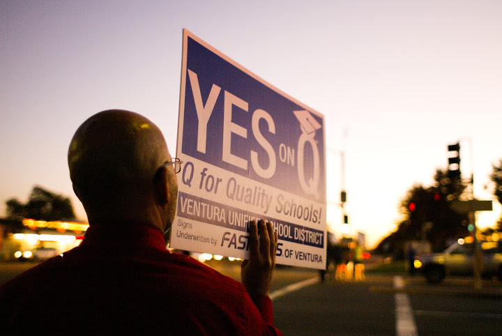 Foothill assistant principal Carlos Cohen shows his support for Measure Q on a Johnson Drive street corner Monday. Credit: Aysen Tan/The Foothill Dragon Press