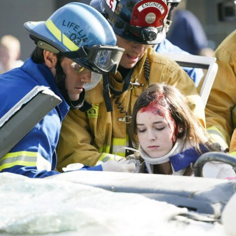 aSenior Marnie Vaughan, who played the part of a critically injured victim in the simulation, is pulled out of a vehicle by firemen. Credit: Aysen Tan/The Foothill Dragon Press