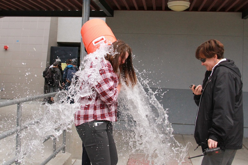 Editor-in-Chief, Rachel Crane, gets doused with water, a tradition started three years ago when the Dragon press won its first Pacemaker. Credit: Aysen Tan/ The Foothill Dragon Press