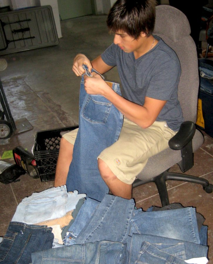 Junior Alex Villapando helps sort jeans for the homeless for Foothills Teen Voice. Photo by Eva Morales, The Foothill Dragon Press.