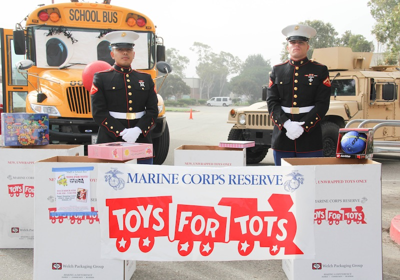 Two marines who volunteered for Toys for Tots stand in front of the bus stuffed on Saturday. Credit: Lauren Pedersen/The Foothill Dragon Press